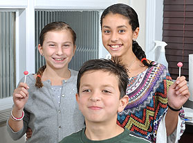 Three Kids Holding Lollipops After Lice Removal